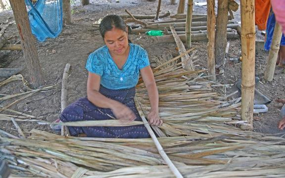 One of the villagers making the thatch for the roofs.