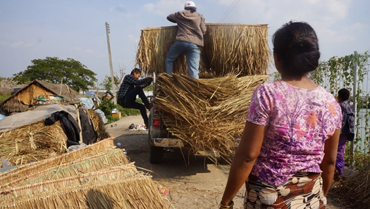 The woman in the foreground makes this thatch roofing. We're helping deliver it to a family who's rebuilding their house.