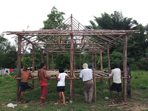 The builders, the headman, a translator, and Fred look at the structure of the new community center and classroom being built on Buddha Land